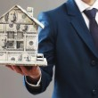 Model of house made of money in male hands on gray background — Stock Photo #69386611