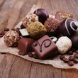 Chocolates assorted on crumble paper with coffee beans on wooden rustic background — Stock Photo #69477549