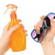 Bottle of suntan spray and sunglasses in female hands isolated on white — Stock Photo #69479143