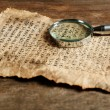 Grunge paper with hieroglyphics with magnifier on wooden background — Stock Photo #69479915