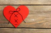 Stitched heart on wooden background — Stock Photo