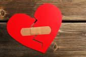 Broken heart with plaster on wooden background — Stock Photo