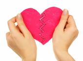 Female hands holding broken heart stitched from two pieces isolated on white — Stock Photo