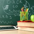 Digital tablet, books, colorful pens and apple on desk in front of blackboard — Stock Photo #69485427