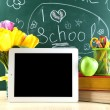 Digital tablet, books, colorful pens and apple on desk in front of blackboard — Stock Photo #69485447