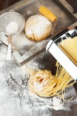 Making vermicelli with pasta machine and sprinkled flour on wooden background — Stock Photo