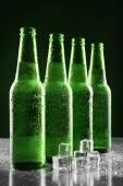 Glass bottles of beer with ice cubes on dark background — Stock Photo