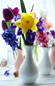 Beautiful bouquets of spring flowers on windowsill background — Stock Photo