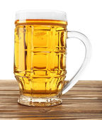 Glass of beer on wooden table, isolated on white — Stock Photo