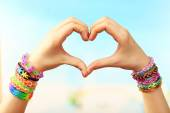 Female hands in shape of heart with bracelets on color blurred background — Stock Photo