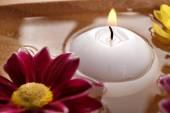 Bowl of spa water with flowers and candle, closeup — Stock Photo