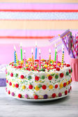 Birthday cake with candle on colorful striped background — Stock Photo