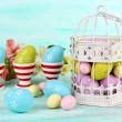 Easter composition with Easter eggs in decorative cage and flowers, on color wooden background — Stock Photo #69490001