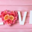 Beautiful roses with word LOVE on pink wooden planks background — Stock Photo #69566093