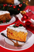 Slice of cake on plate with fork on table with Christmas decoration background — Stock Photo