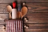 Set of kitchen utensils in mitten on wooden planks background — Stock Photo