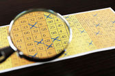 Analyzing lottery ticket with magnifier — Fotografia Stock