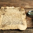 Grunge paper with hieroglyphics with magnifier on wooden background — Stock Photo #69701047