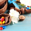 Chocolate Easter eggs with flowers on wooden table, closeup — Stock Photo #69705735