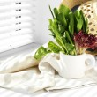 Watering can with variety of green leaves for salad on windowsill — Stock Photo #69706721