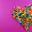 Colorful candies in heart shape on purple background — Stock Photo #69707959