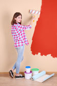Beautiful woman paints wall in room — Stock Photo