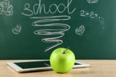 Digital tablet and apple on  desk in front of blackboard — Stock Photo
