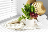 Watering can with variety of green leaves for salad on windowsill — Stock Photo