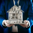 Model of house made of money in male hands on dark background — Stock Photo #69726645
