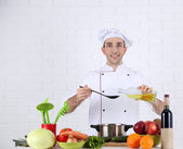 Chef at table with different products and utensil in kitchen on white wall background — Stock Photo