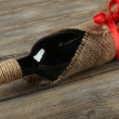Red wine bottle wrapped in burlap cloth on wooden planks background — Stock Photo #69959275