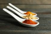 Different kinds of spices in spoons on wooden background — Stock Photo