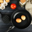 Still life with eggs and pan on wooden table, top view — Stock Photo #69961167