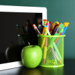 Digital tablet, books, colorful pens and apple on desk in front of blackboard — Stock Photo #69962879