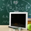 Digital tablet, books, colorful pens and apple on desk in front of blackboard — Stock Photo #69962881
