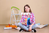 Beautiful girl sitting on floor with equipment for painting wall — Stock Photo