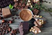 Set of chocolate with nuts, herbs and coffee beans on wooden table, closeup — Stock Photo