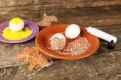 Decorating Easter eggs on color plate on wooden table, closeup — Stock Photo