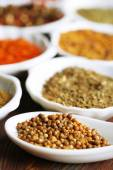 Different kinds of spices in ceramics spoons, close-up, on wooden background — Stock Photo