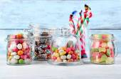 Multicolor candies in glass jars on color wooden background — Stock Photo