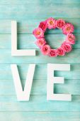 Beautiful roses with word LOVE on color wooden planks background — ストック写真