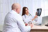 Médecins recevant les résultats de la radiographie au bureau sur fond blanc — Photo