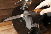 Afiador de facas e mão com lâmina na mesa de madeira, closeup — Fotografia Stock