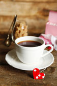 Heart shaped teabag tags and Cup of tea with on wooden background — Stock Photo