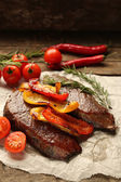 Composition with tasty roasted meat on paper sheet, tomatoes and rosemary sprigs on wooden background — Stock Photo