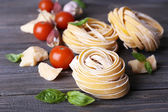 Raw homemade pasta with cheese and vegetables on wooden background — Stock Photo