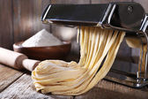 Making noodles with pasta machine on wooden background — Stock Photo