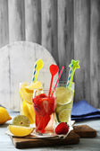 Cocktails with fresh strawberries and lemon lime on wooden background — Stock Photo