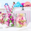 Multicolor candies in glass jars and cupcakes on color wooden background — Stock Photo #70233115