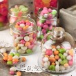 Multicolor candies in glass jars and cupcakes on wooden background — Stock Photo #70233133